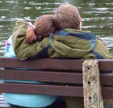 a couple on a bench in fron of a lake